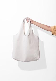 La muchacha está sosteniendo la tela de lona del bolso para la plantilla en blanco de la maqueta en el fondo blanco