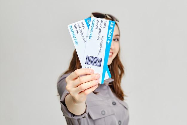 La muchacha sostiene boletos de avión adelante con una sonrisa.