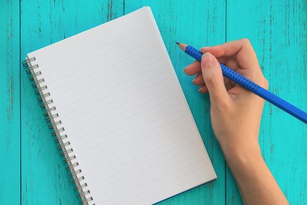 La muchacha sostiene el lápiz, se prepara para anotar metas para el futuro en el cuaderno, tabla de madera azul.