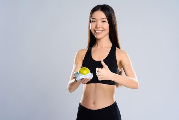 La muchacha sostiene la manzana verde y muestra la muestra estupenda.