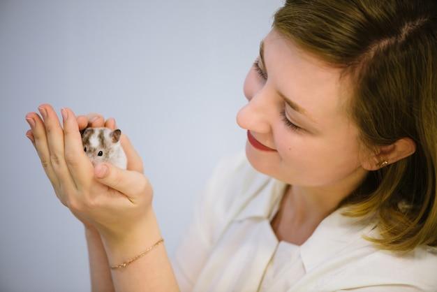 La muchacha sostiene el pequeño ratón peludo blanco en el fondo blanco. lindos ratones jóvenes en manos de veterinario. pequeña rata blanca con manchas marrones. hermoso ratón manchado curioso. tímida mascota al veterinario. animal gracioso