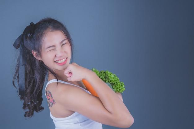 La muchacha sostiene las verduras en un fondo gris.