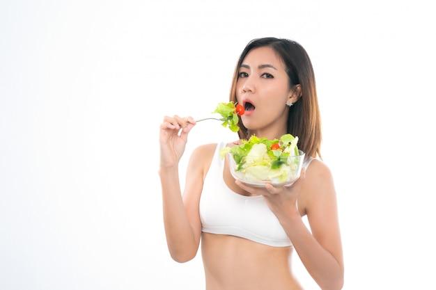 La muchacha en un sujetador blanco del deporte sostiene un cuenco de ensalada.