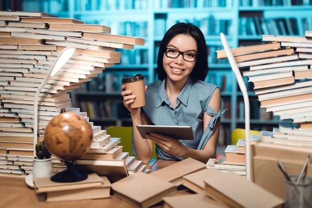Muchacha con la tabla rodeada por los libros en biblioteca en la noche.