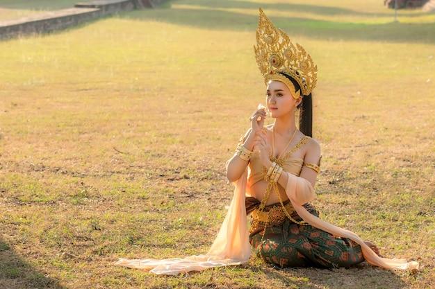 Muchacha tailandesa de las mujeres hermosas en traje tailandés tradicional con el templo ayutthaya.