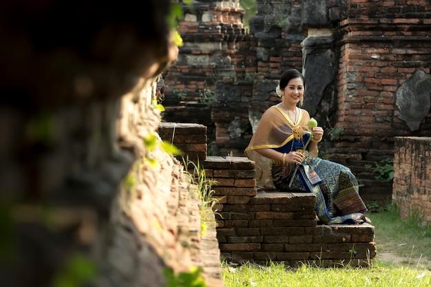 Muchacha tailandesa que sostiene loto de la mano en el traje tailandés tradicional con el templo ayutthaya