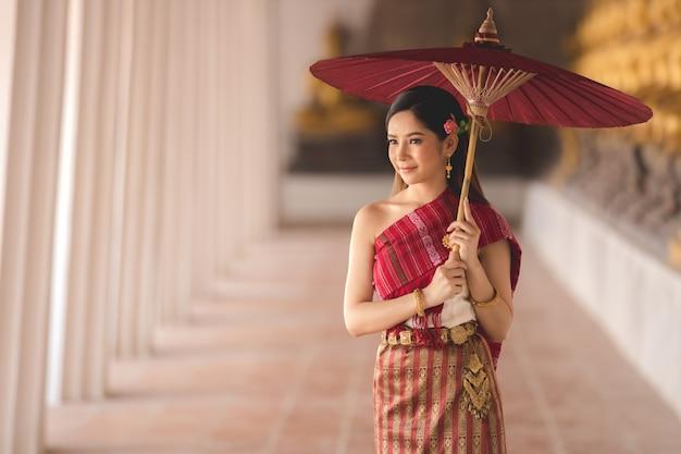Muchacha tailandesa en traje tailandés tradicional con el paraguas rojo en el templo tailandés, cultura de identidad de tailandia.