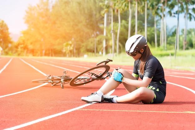La muchacha tiene un accidente deportivo injur en su rodilla del concepto de la bicicleta, del deporte y del accidente
