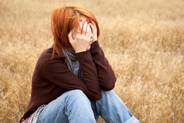 Muchacha triste del pelirrojo que se sienta en hierba amarilla en el campo
