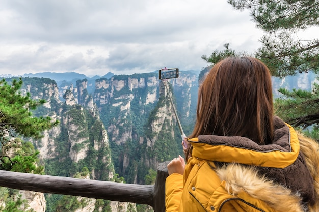 Muchacha turística asiática que toma la foto usando el teléfono inteligente zhangjiajie wulingyuan changsha china