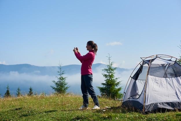 Muchacha turística feliz que se coloca en el valle herboso floreciente delante de la pequeña tienda turística y que toma la imagen de montañas hermosas cubiertas con las nubes blancas debajo del cielo azul claro en la mañana brillante del verano.