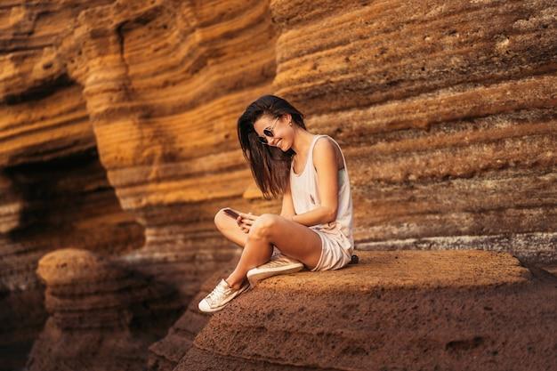 La muchacha turística morena del pelo bastante largo que se relaja en las piedras acerca al mar.