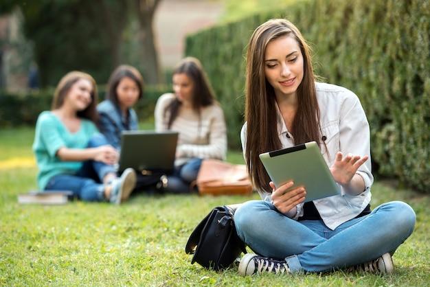 La muchacha de universidad sonriente está sosteniendo la pc de la tableta.
