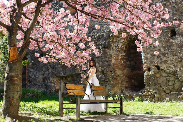 La muchacha en el vestido blanco se coloca debajo de árbol floreciente rosado de sakura en el parque