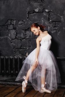 Muchacha en un vestido de bola blanco y zapatos