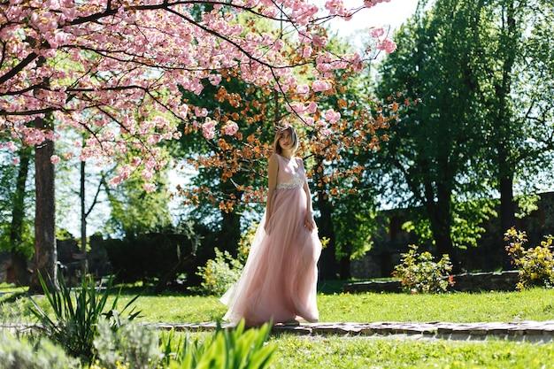 La muchacha en vestido rosado se coloca bajo árbol floreciente de sakura en el parque