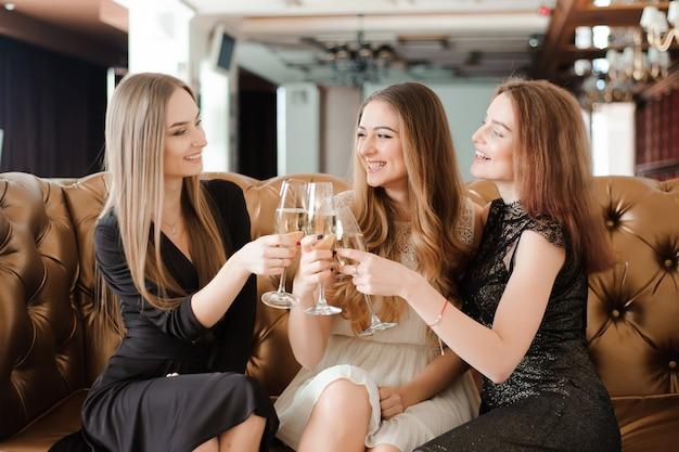 Muchachas alegres que tintinean los vidrios de champán en la fiesta.