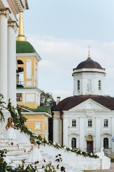 Las muchachas de las flores caminan arriba antes de la vieja iglesia rusa
