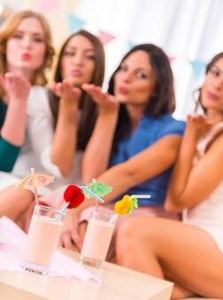 Las muchachas hermosas jóvenes beben cócteles en casa fiesta.
