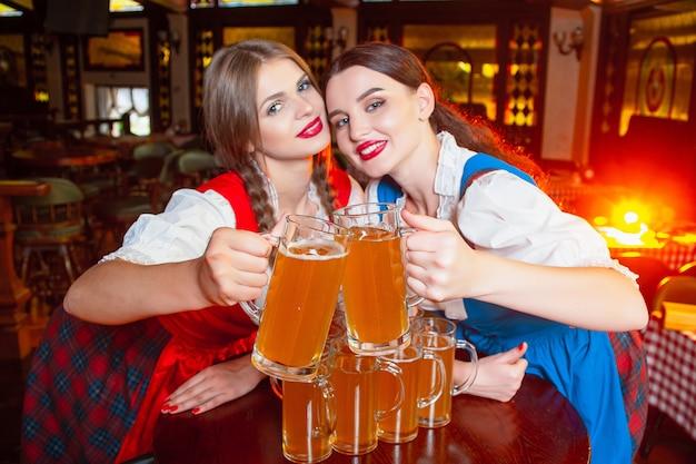 Las muchachas hermosas tintinean los vasos con cerveza en el festival oktoberfest.