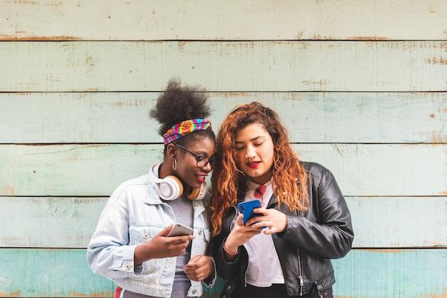 Muchachas multirraciales del adolescente que usan el teléfono móvil al aire libre.