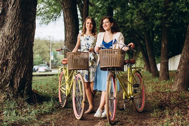 Muchachas positivas y felices que caminan con las bicicletas en el parque del callejón, día de verano. amigas disfrutando de un paseo por la calle con sus bicicletas.