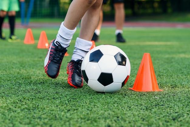 El muchacho adolescente aprende a rodear la pelota entre los conos de entrenamiento en el estadio de fútbol.