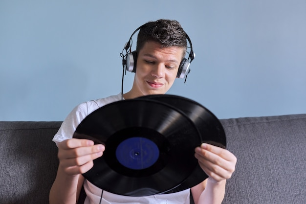 Muchacho adolescente creativo con discos de vinilo, joven en auriculares interesado en música, pasatiempos y ocio, fondo gris