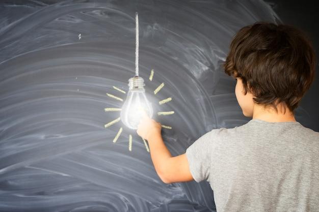 Muchacho adolescente encontrar una idea con bombilla incandescente - concepto de educación de regreso a la escuela