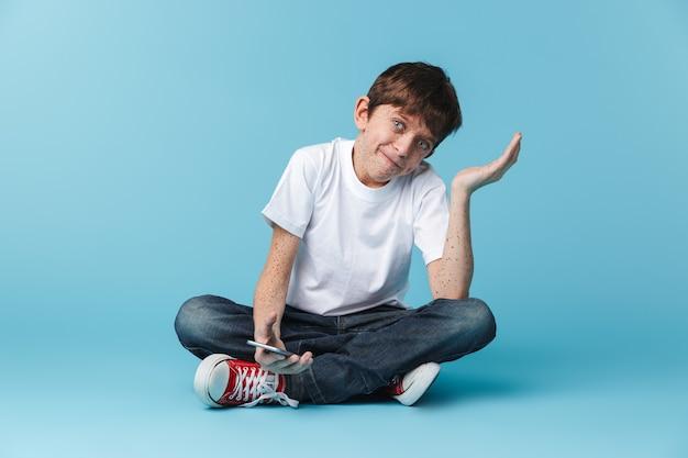 De muchacho adolescente europeo con pecas vistiendo camiseta blanca casual sosteniendo y usando el teléfono inteligente mientras está sentado en el piso aislado sobre la pared azul
