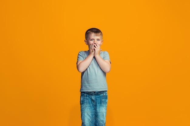 El muchacho adolescente feliz de pie y sonriendo contra el espacio naranja.