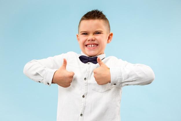 Muchacho adolescente feliz sonriendo aislado en estudio azul
