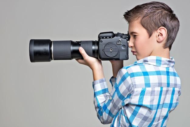 Muchacho adolescente con la fotografía de la cámara réflex digital. niño con cámara tomando fotografías. retrato de perfil.