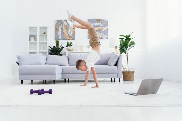 Muchacho adolescente haciendo ejercicios de pie de manos en la acogedora sala de estar.