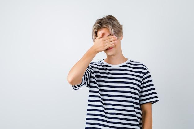 Muchacho adolescente joven con la mano en la cara en camiseta rayada y mirando avergonzado. vista frontal.