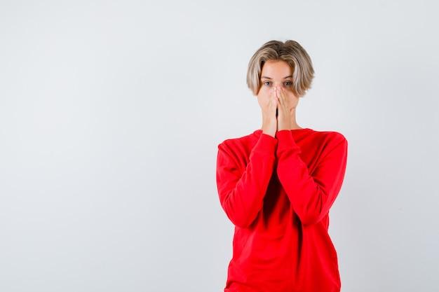 Muchacho adolescente joven con las manos en la cara en suéter rojo y mirando emocionado, vista frontal.