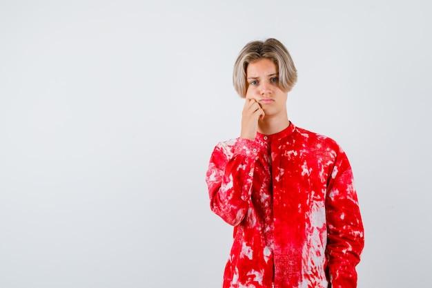 Muchacho adolescente joven que se inclina la mejilla en la mano en camisa y mirando molesto, vista frontal.