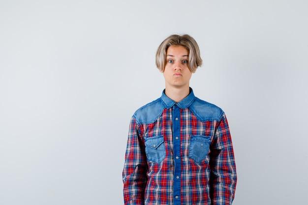 Muchacho adolescente joven que mira la cámara en camisa a cuadros y que parece desconcertado. vista frontal.
