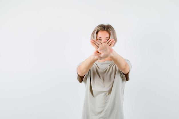 Muchacho adolescente joven que muestra el gesto de la negativa en camiseta y que parece resuelto. vista frontal.