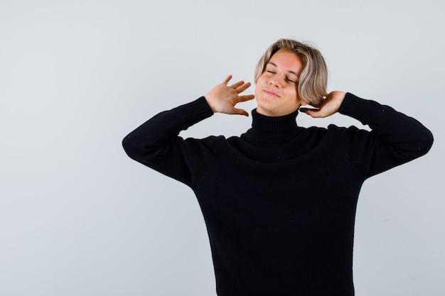 Muchacho adolescente lindo que estira la parte superior del cuerpo en un suéter de cuello alto negro y que parece relajado. vista frontal.