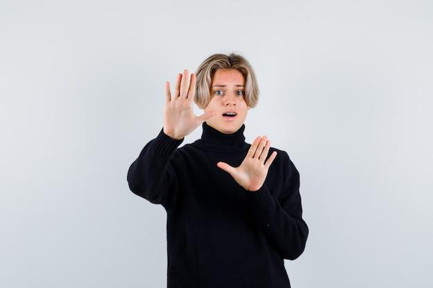 Muchacho adolescente lindo que muestra el gesto de la rendición en suéter de cuello alto negro y que parece aterrorizado. vista frontal.