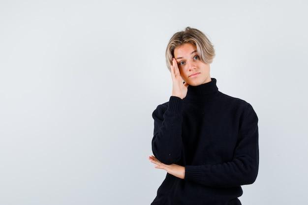 Muchacho adolescente lindo en suéter de cuello alto negro con la cabeza inclinada en la mano y mirando pensativo, vista frontal.