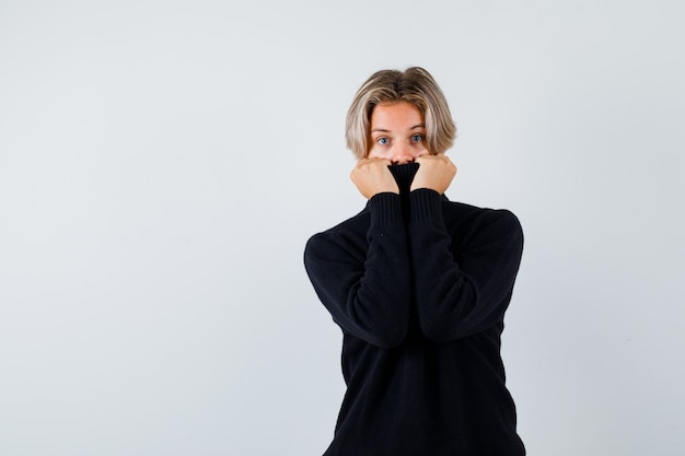 Muchacho adolescente lindo en suéter de cuello alto tirando del cuello en la cara y mirando asustado