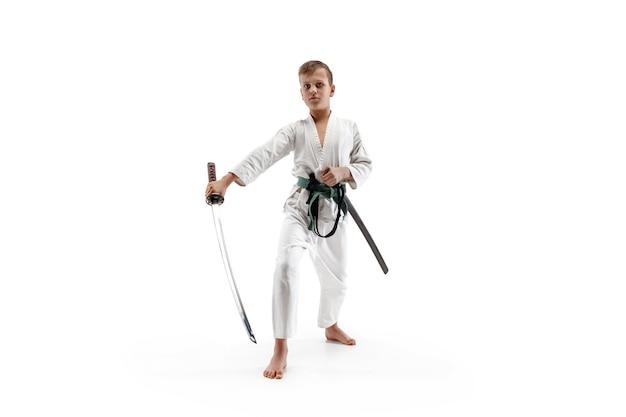 Muchacho adolescente luchando en el entrenamiento de aikido en la escuela de artes marciales