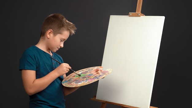 El muchacho adolescente pintor joven creativo mezcla pinturas al óleo en la paleta mientras está de pie delante de un lienzo en blanco sobre un caballete. concepto de dibujo. recortar sobre fondo gris. copie el espacio.