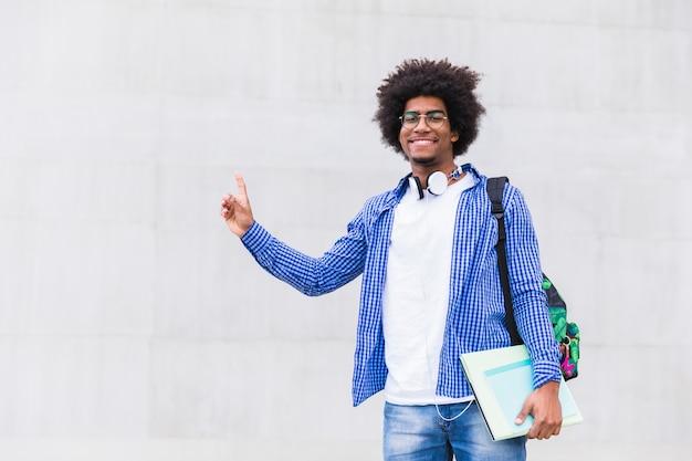 Muchacho adolescente que sostiene libros en la mano que señala su dedo hacia arriba contra el muro de cemento blanco