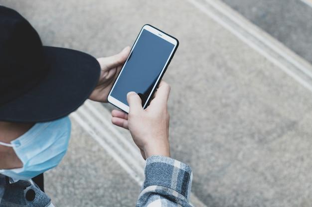Muchacho adolescente que usa el dispositivo del teléfono inteligente para la tecnología de red en línea internet; el hombre usa el móvil en el parque público.