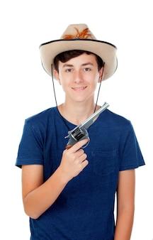 Muchacho adolescente con sombrero de vaquero y pistola.