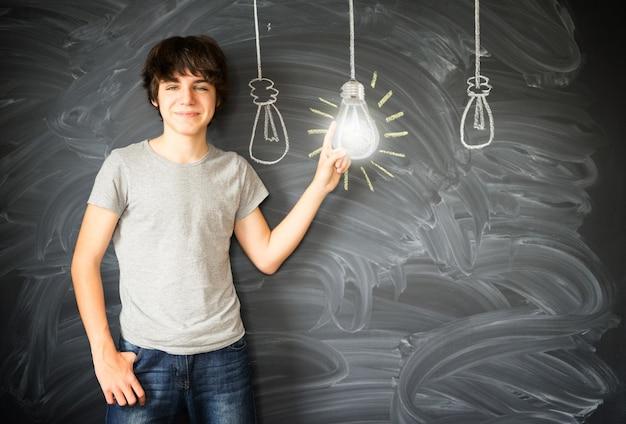 Muchacho adolescente teniendo una idea con fila de bombillas