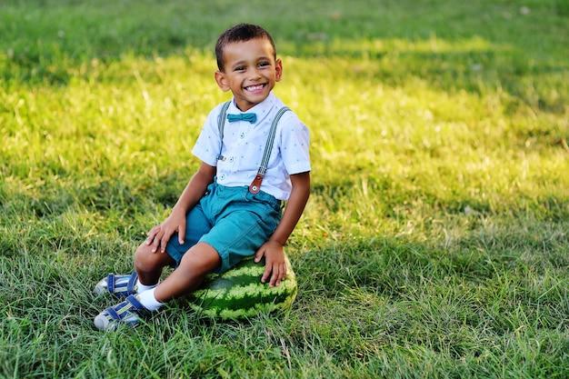 Muchacho afroamericano negro lindo que se sienta en una sandía enorme y que sonríe en un parque